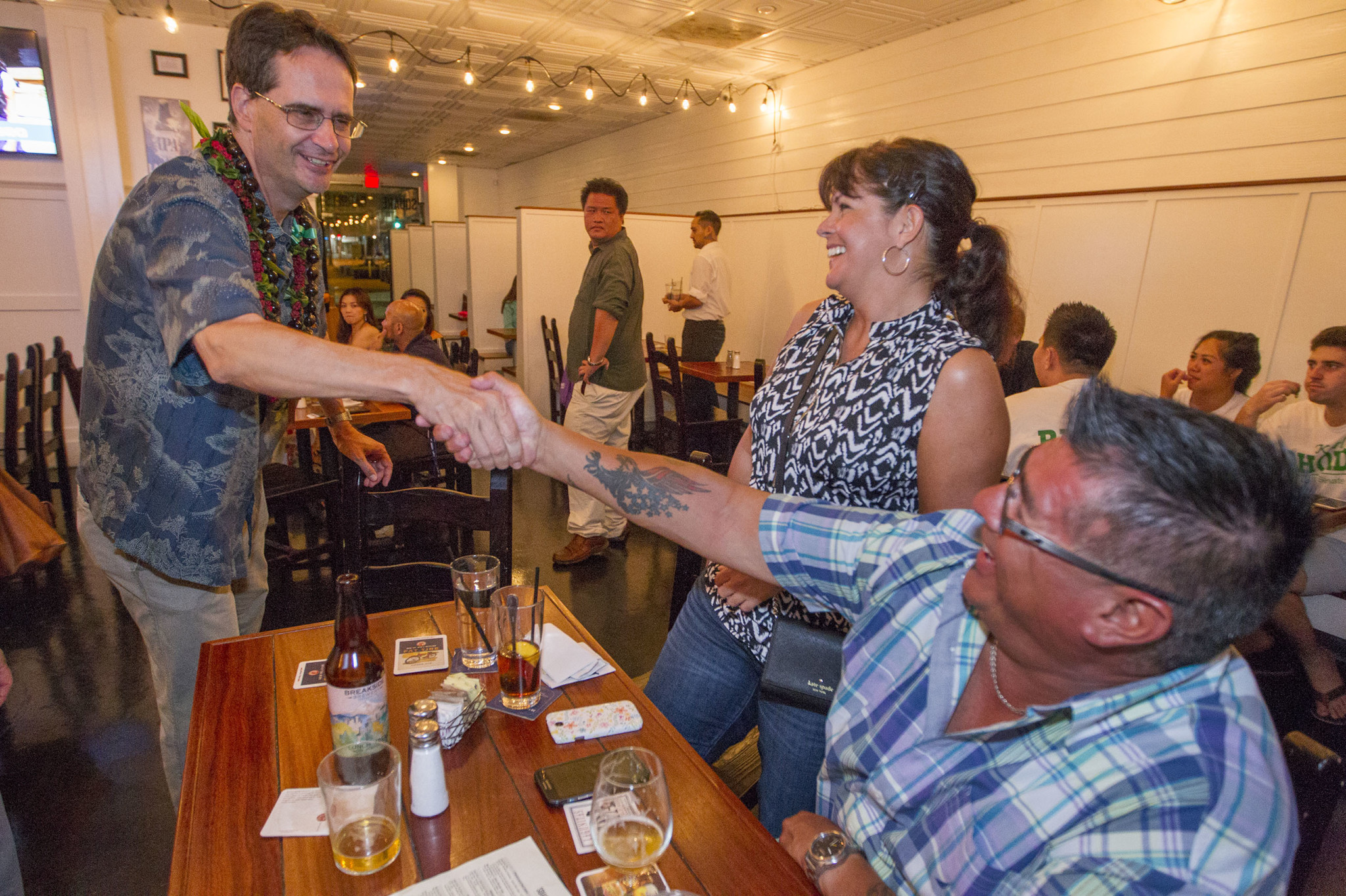 <p>Rep. Karl Rhoads, left, was looking to move from the state House to the Senate, and celebrated winning the District 13 Democratic primary with supporters at Square Barrels downtown. (Eugene Tanner/Civil Beat)</p>