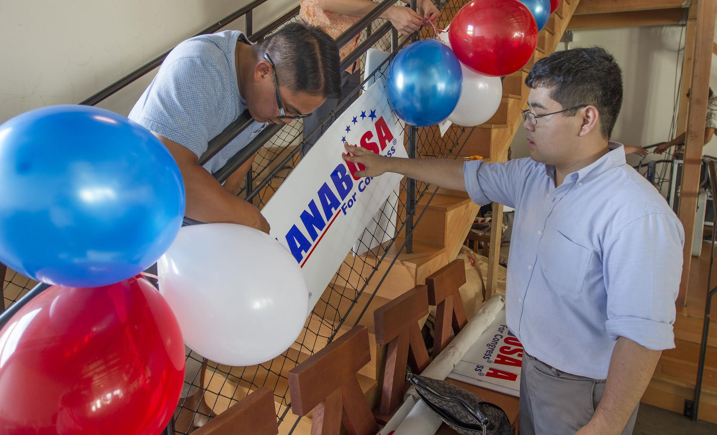 <p>By afternoon, campaign workers were preparing for parties. Volunteers Rufino Magliba, left, and Chris Murata helped prepare the election night headquarters of congressional candidate Colleen Hanabusa. (Eugene Tanner/Civil Beat)</p>
