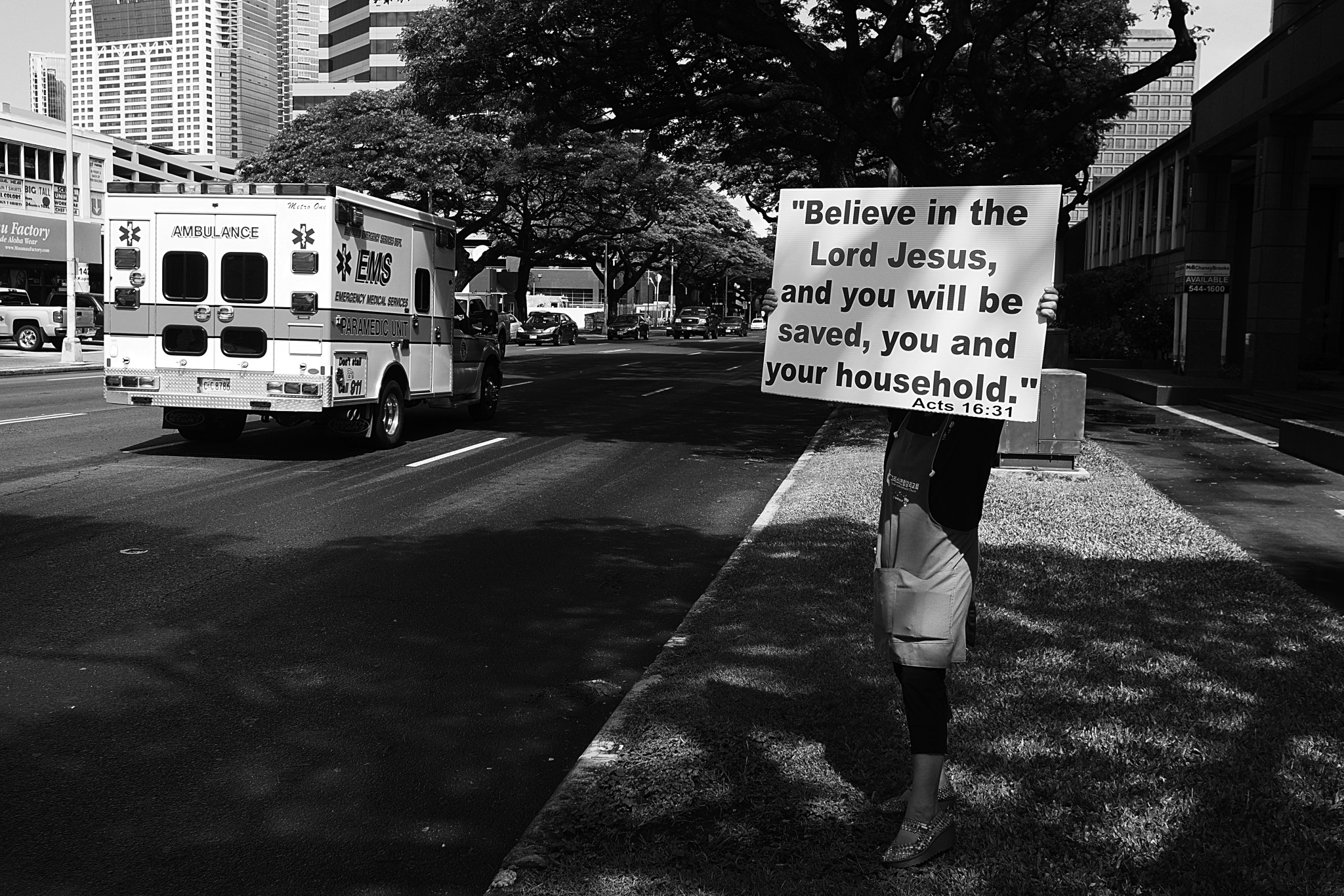 <p>Could the sign borne by a woman on Keeamouku Street have been a message for the occupant of a passing ambulance?</p>
