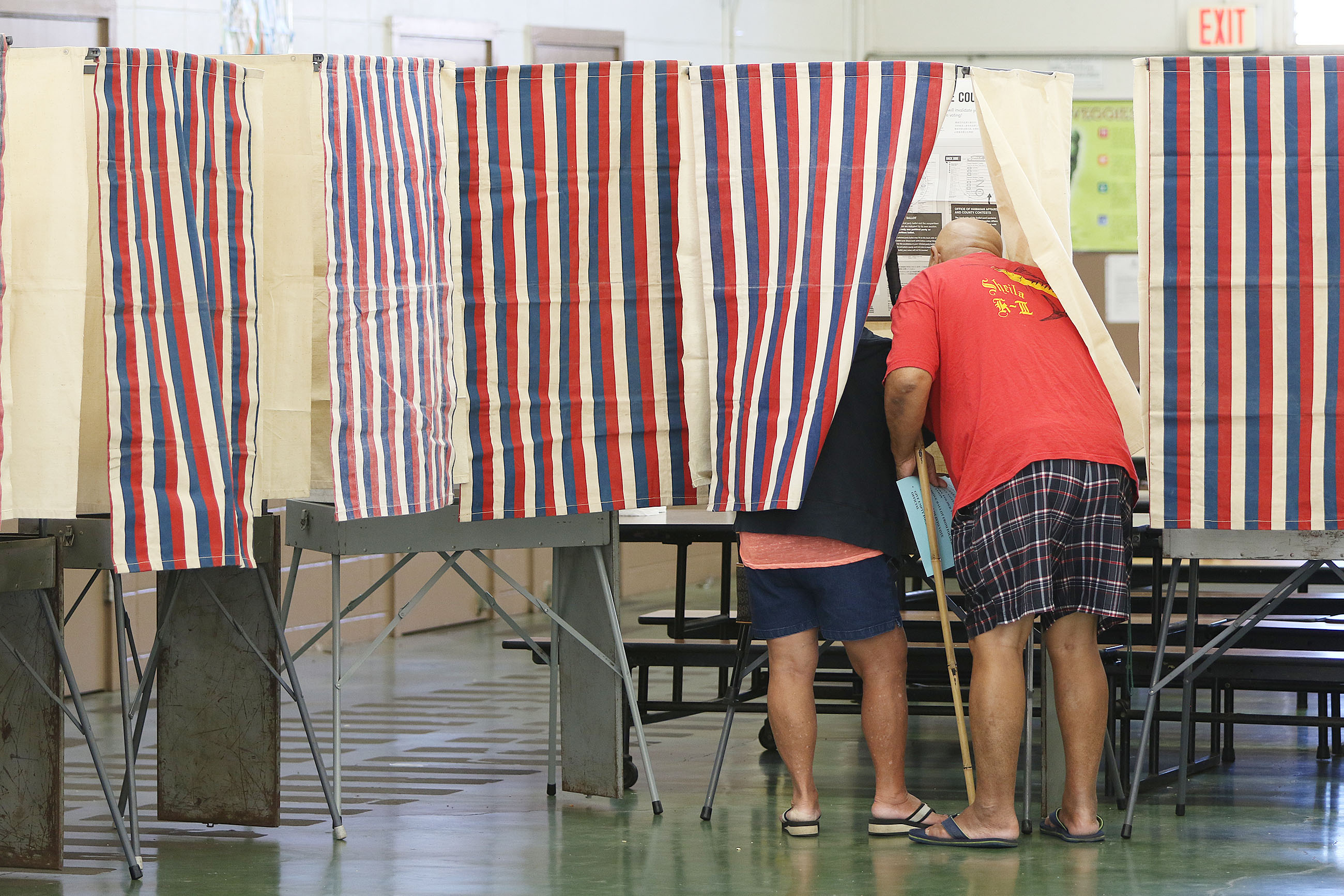 <p>Even though all the other booths were available, a couple voted in just one early Saturday at Kawananakoa Middle School. (Cory Lum/Civil Beat)</p>