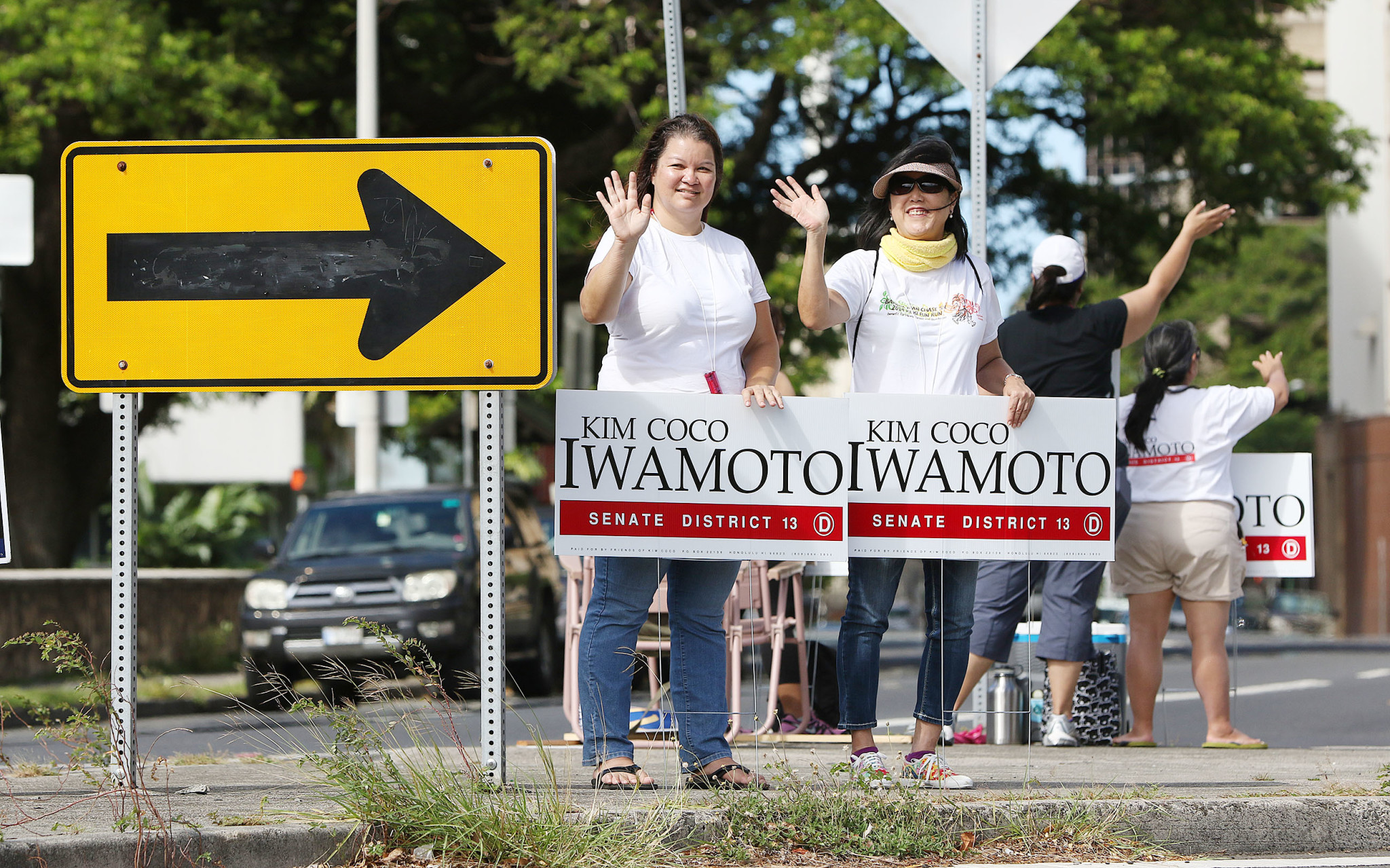 <p>All day, sign-wavers urged passersby to vote. With a record low voter turnout, most obviously chose not to. Dawn Nekoba, left, and Lynda Camarao displayed their support for Kim Coco Iwamoto's state Senate campaign near Central Middle school. (Cory Lum/Civil Beat)</p>