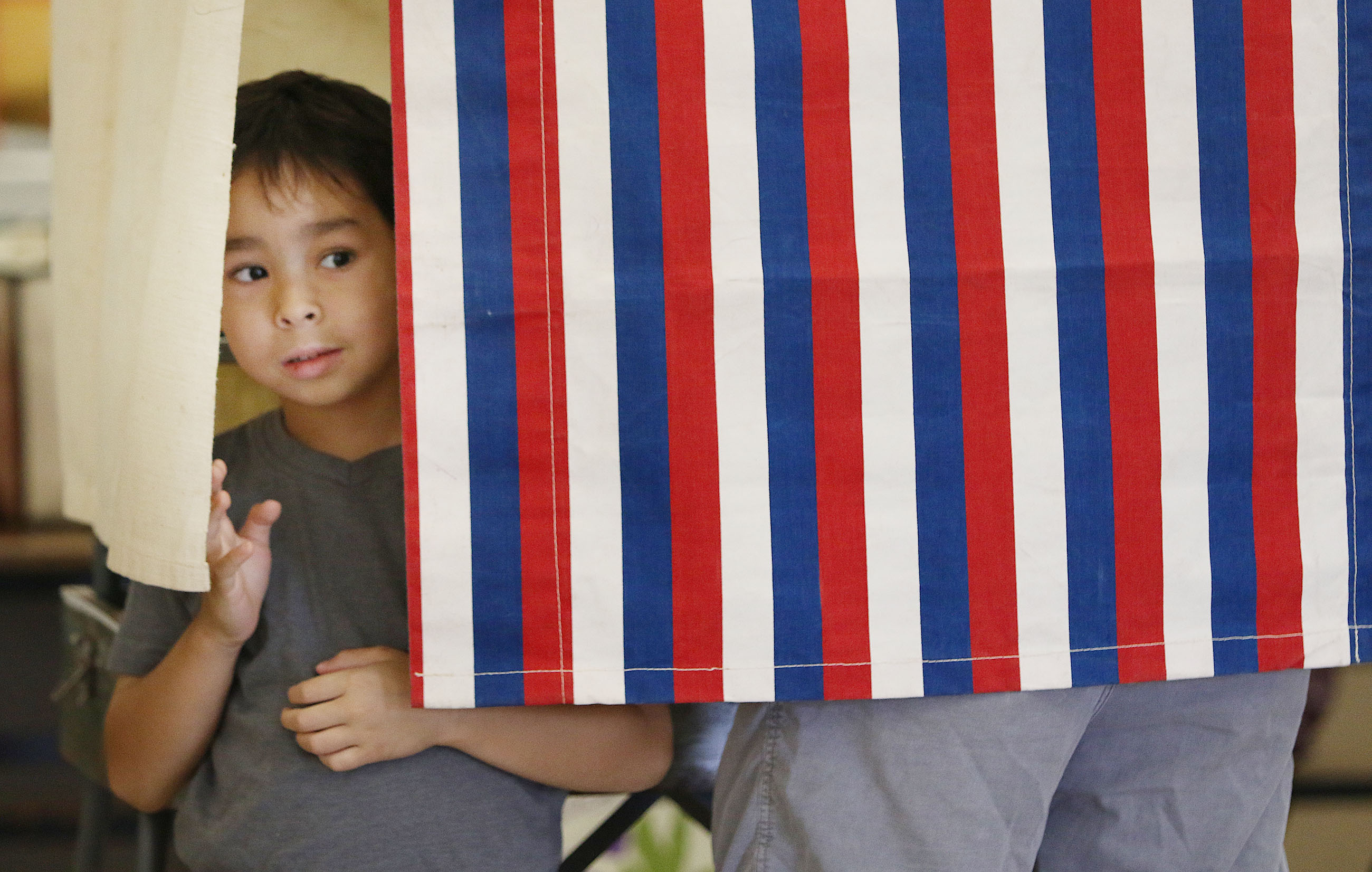 <p>Luke Herring, 5, checked out the inaction as his father, Kevin Herring, voted in the Central Middle School cafeteria. (Cory Lum/Civil Beat)</p>