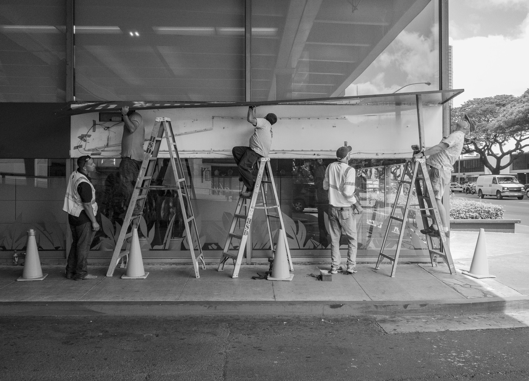 <p>Teamwork and synchronization came into play as men worked on a sign outside a Bank of Hawaii building.</p>