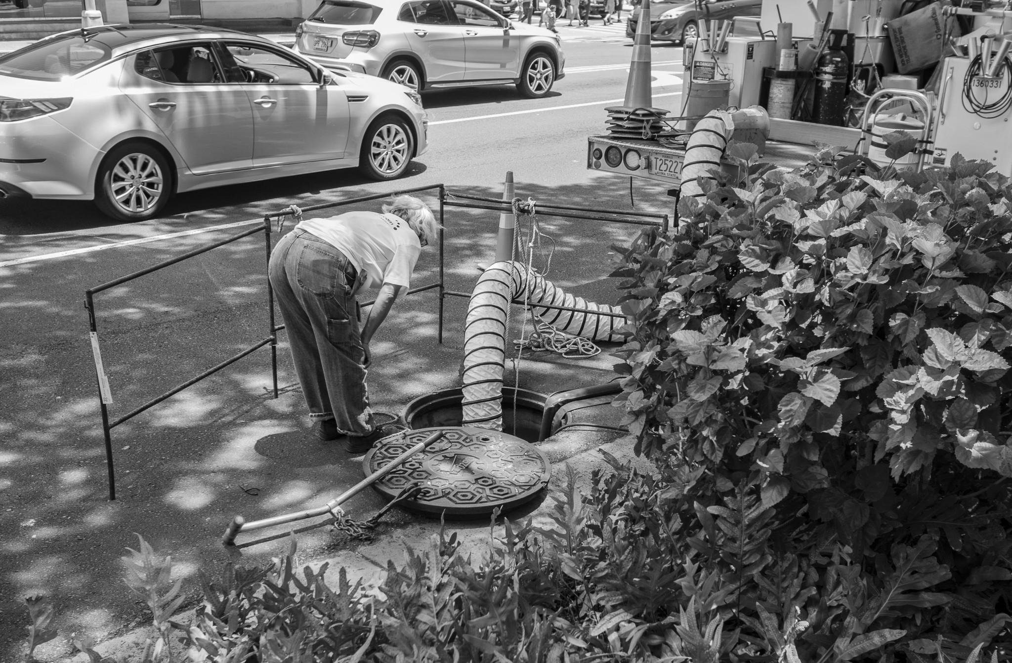 <p>A Hawaiian Telcom employee peered down an open manhole as utility work was done on Keeaumoku Street.</p>