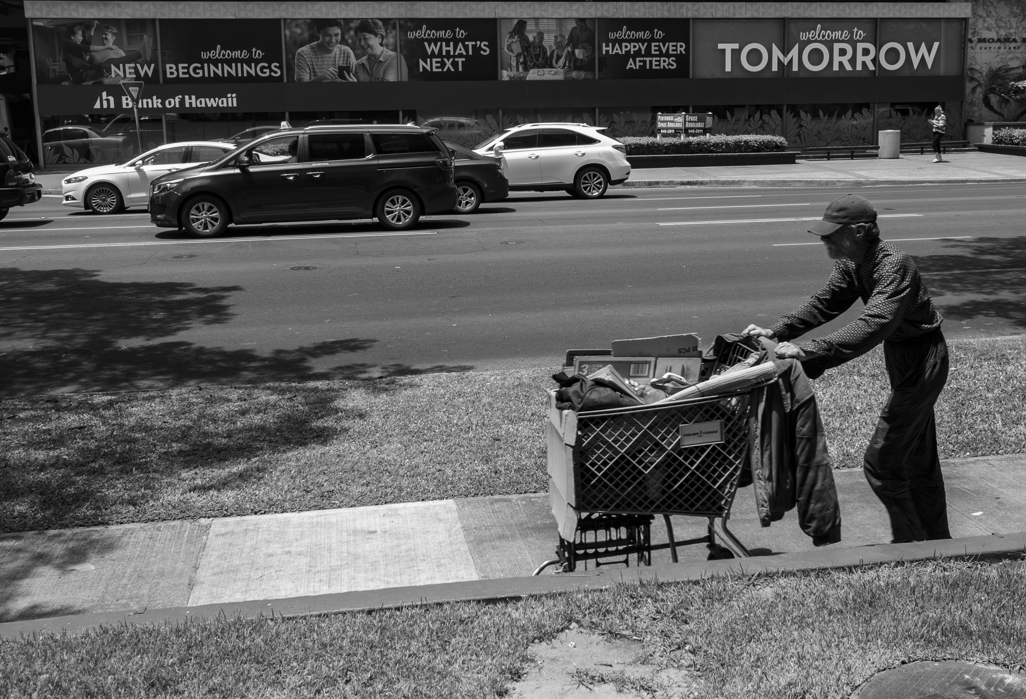 <p>A man rolled his possessions past some hopeful economic messages outside a bank building.</p>