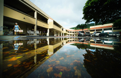 Manoa Marketplace water reflections with shopper talking by with Manoa Safeway grocery bag. 9 sept 2016.