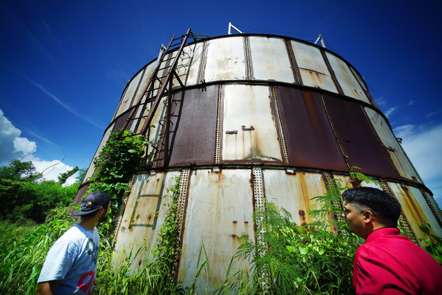 Tom Pangelinan and Robert Deleon Guerrero stand below a large fuel tank that needs to be cleaned up. 24 aug 2016