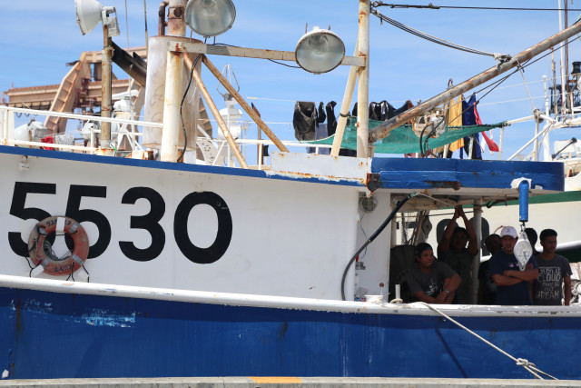 Fishermen watch a rally in July from a longline fishing vessel at Pier 38 in Honolulu.