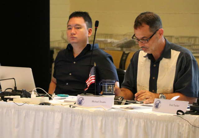 Michael Goto, left, of the United Fishing Agency, and Michael Tosatto, regional administrator of the National Marine Fisheries Service, listen during a Western Pacific Regional Fishery Management Council meeting, Oct. 13, 2016, in Honolulu.