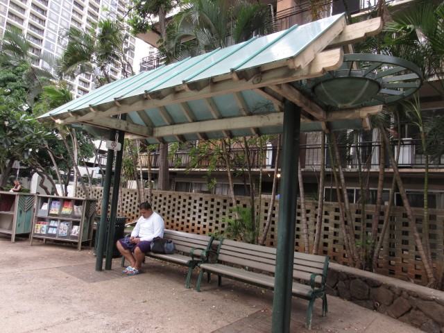 Sam Filipo, a cook at Queen Kapiolani Hotel, awaits his evening bus to go home to Waianae.