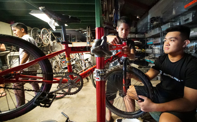 Right, KVIBE senior intern, 15-year-old Randell Dejesus from Farrington HS assists 10-year-old Wally Jakabot at the Kalihi Valley Instructional Bicycle Exchange Program. 26 oct 2016