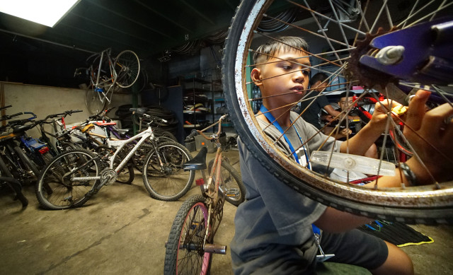 10-year old Sebastian Supapo works on the rear wheel of a bike at KVIBE Kalihi Valley Instructional Bicycle Exchange Program. Natanya story. 26 oct 2016.