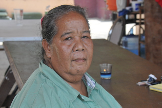 Clotilde Aldan sits outside her house on Saipan. She says she wants her grandchildren to be able to live on Pagan.