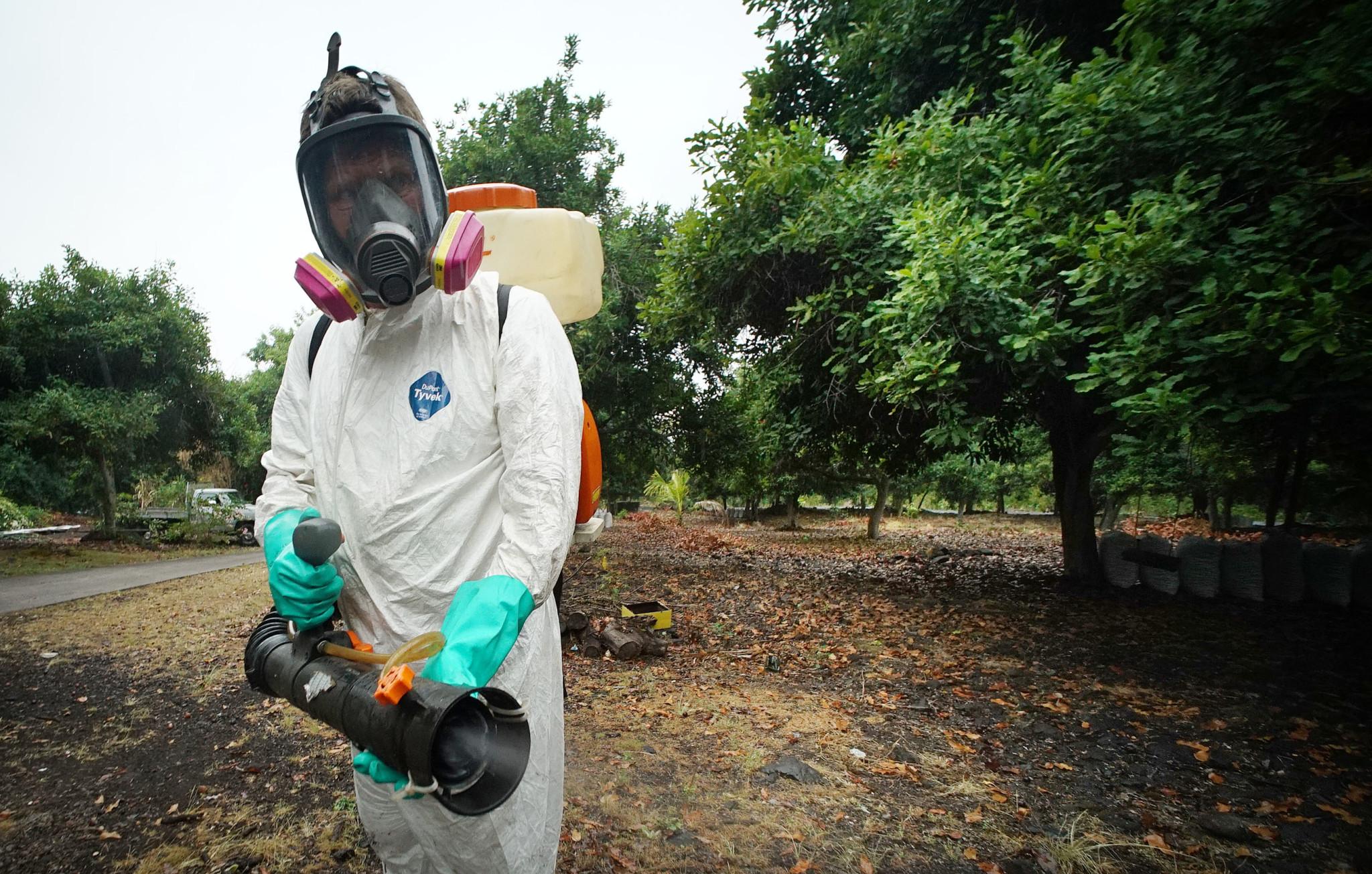 <p>Feb. 18: Big Island resident Bill Cullum uses a gas-powered sprayer to combat mosquitoes during a dengue fever outbreak. <em>Cory Lum/Civil Beat</em></p>