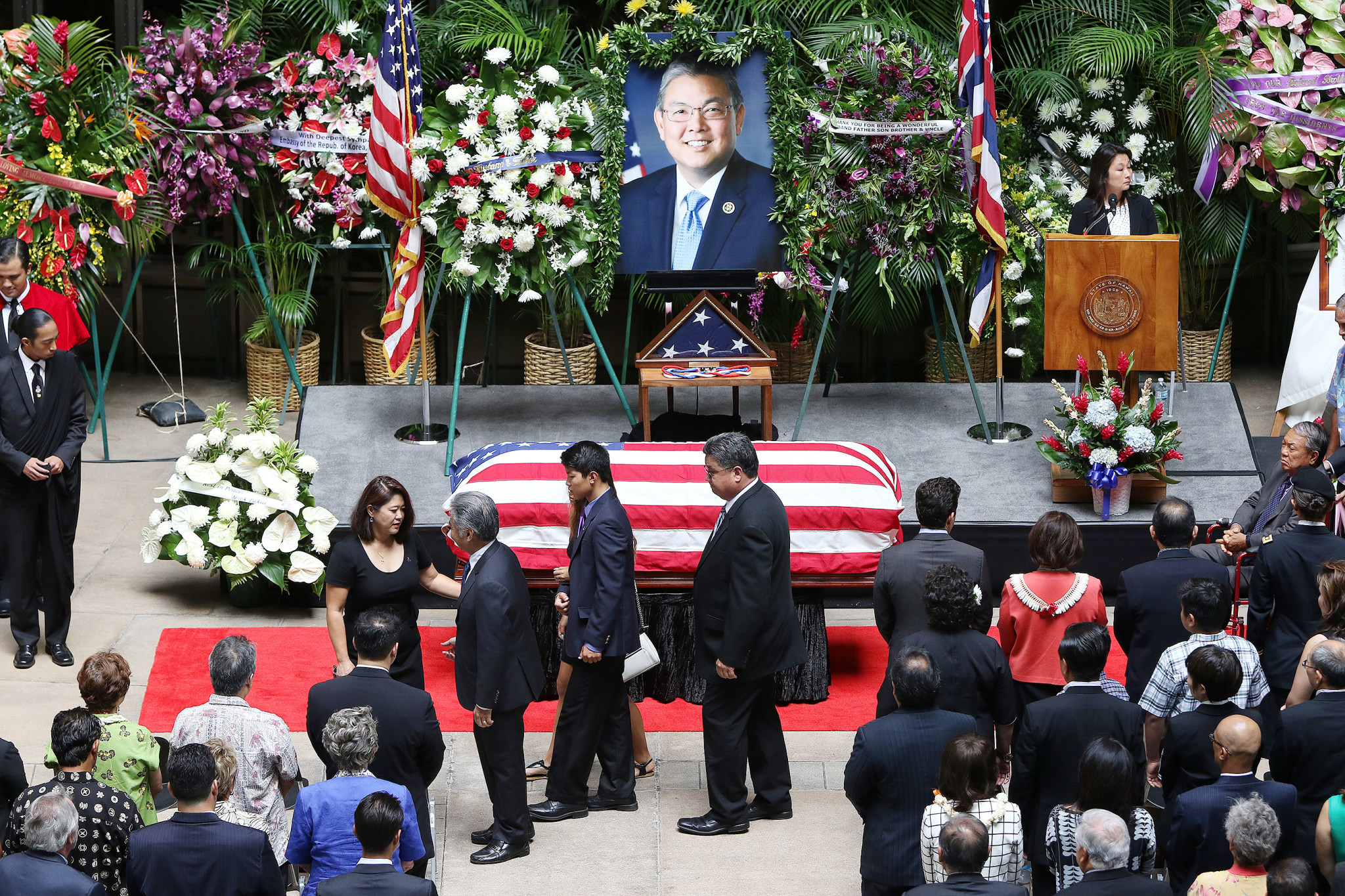 <p>Aug. 18: The late U.S. Rep. Mark Takai's casket rests in the Capitol Rotunda as his wife, Sami, greets Gov. David Ige during a memorial service. After serving 20 years in the state House of Representatives, Takai, 49, was unable to complete his first full term in Congress. <em>Cory Lum/Civil Beat</em></p>