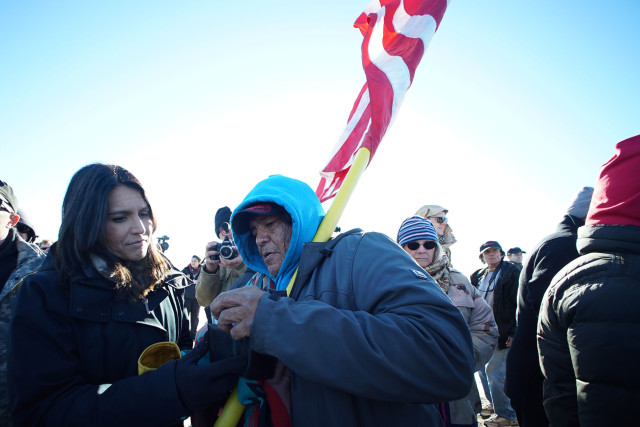 Ernest Aleita from Ctownpoint, New Mexico speaks to Congresswoman Tulsi Gabbard during veterans supporting Standing Rock demonstrators at a field near Cannonball, N Dakota. 4 dec 2016