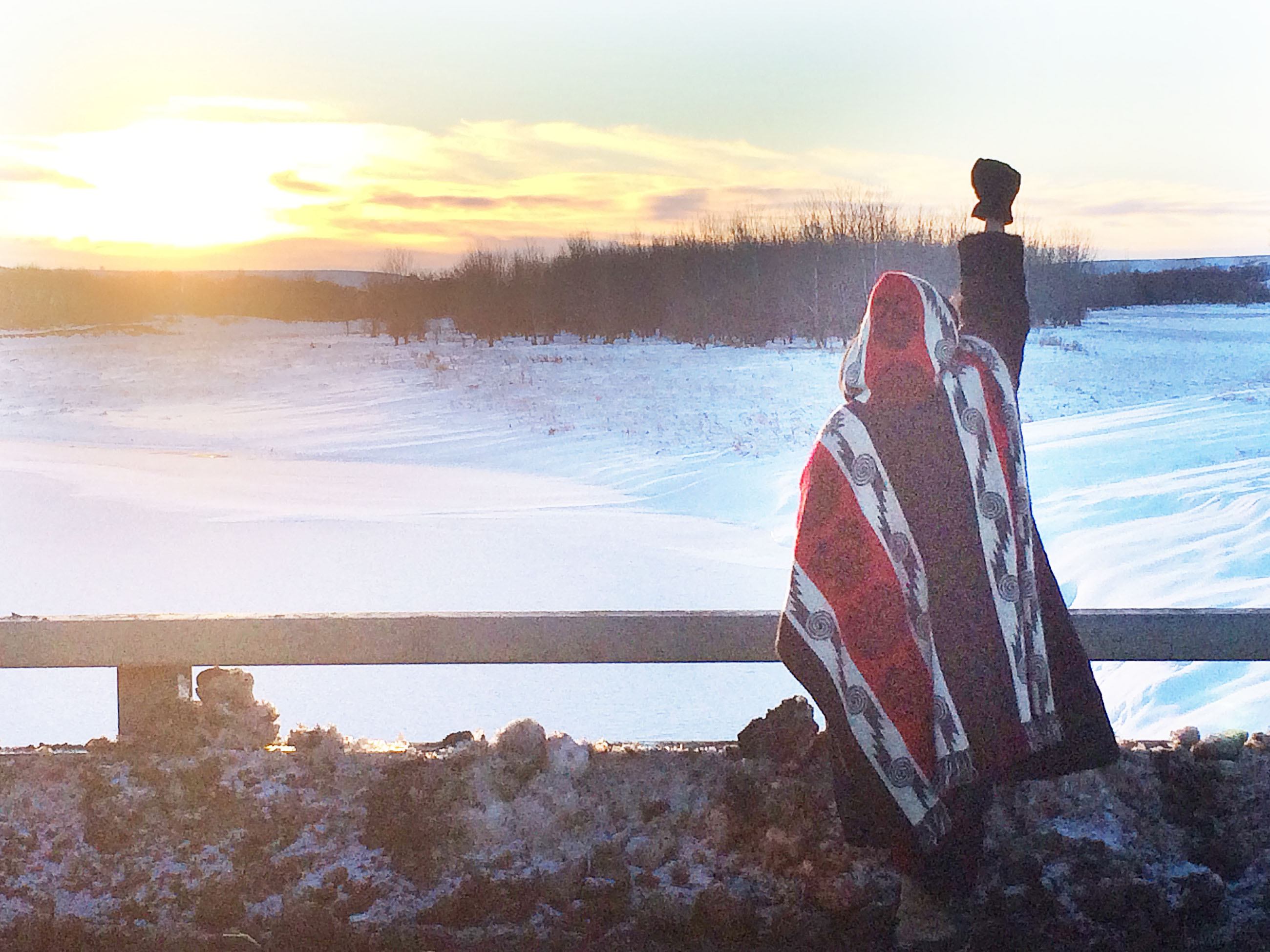 <p>A protester took in the scene as the sun set at Standing Rock on one of the last days before a blizzard hit.</p>