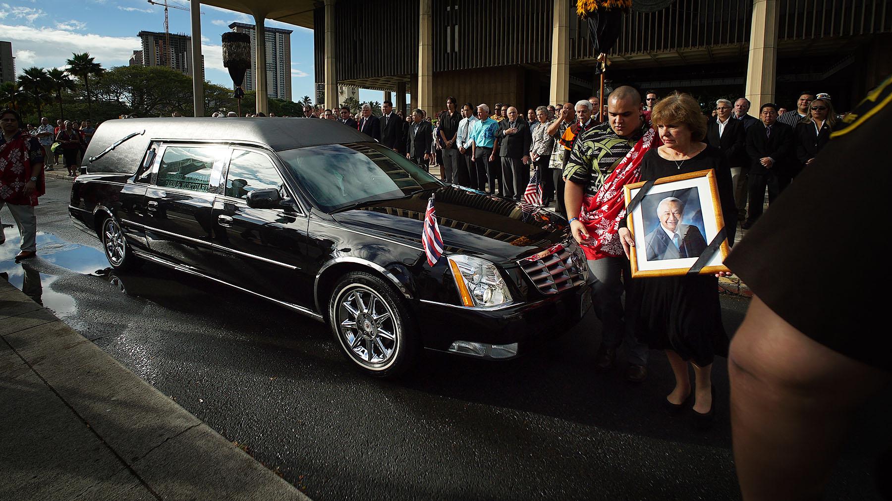 <p>Feb. 2: The late Sen. Gil Kahele's wife, Linda, watches as a hearse carrying the body of the Big Island legislator reaches the Capitol. <em>Cory Lum/Civil Beat</em></p>