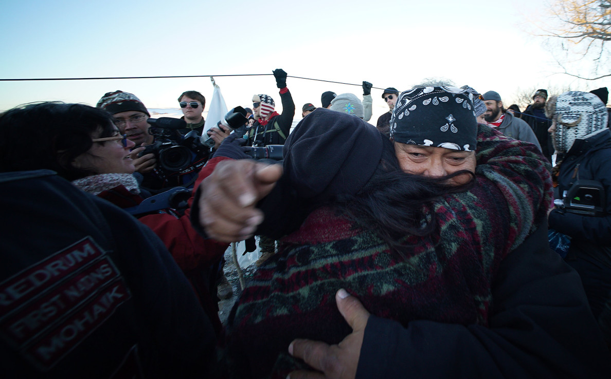 After speaking at length about unifying Standing Rock supporters on Hwy 1806, near the bridge, elder Troy Fairbanks hugs a supporter. Mood was somber and cautious after the announcement. 4 dec 2016