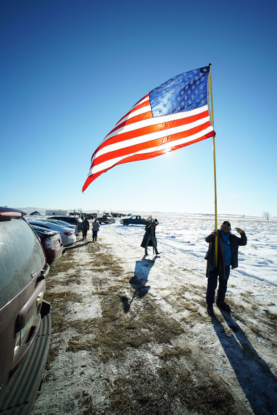 Ernest Aleita from Ctownpoint, New Mexico walks with a large flag after veterans supporting Standing Rock demonstrators at a field near Cannonball, N Dakota. 4 dec 2016