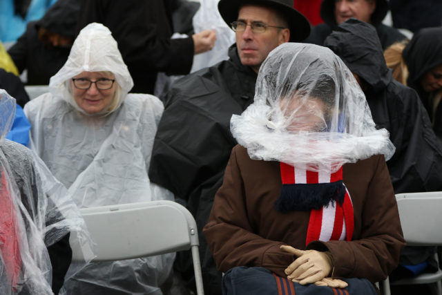 Collene Goldman from Dallas, Texas uses a plastic bag to protect her head from a slight drizzle during Trump Inauguration 2017 near the Capitol building. 20 jan 2017