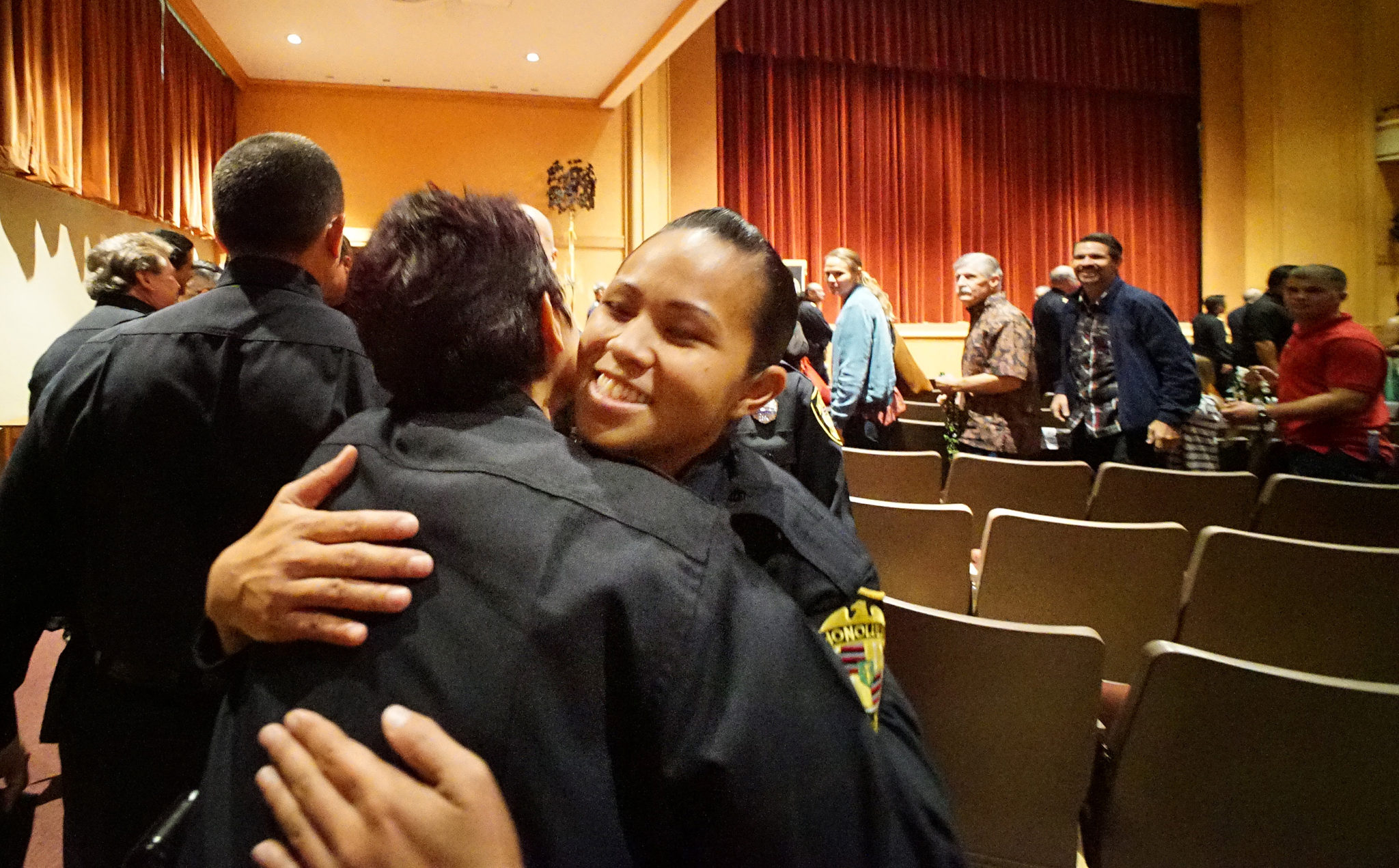 <p>HPD Chaplain Annie Forester, left, hugged new graduate Tani Takushi after the ceremony.</p>