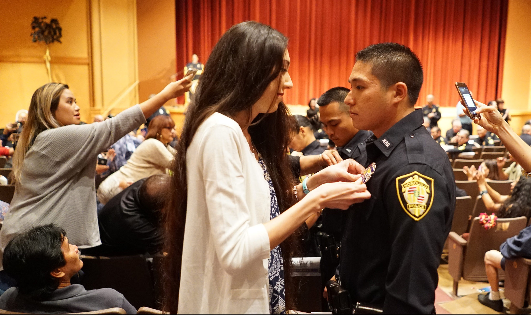 <p>Jason Yee Hoy, right, was among 17 recruits who got their badges just before the graduation ceremony Wednesday night at McKinley High School. They will now partner up with veteran officers to gain field experience.</p>