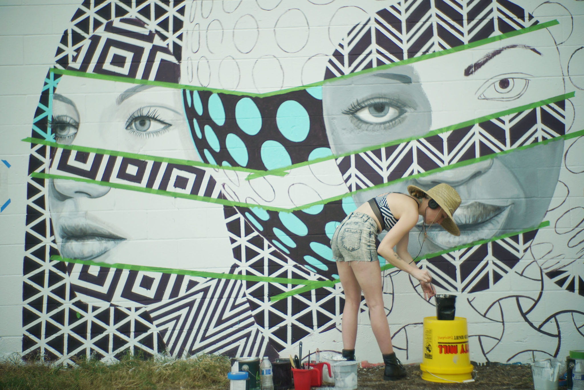"<p>Michelle Tanguay of Detroit works on her mural, ""Love Thy Neighbor,"" along Auahi Street.</p>"