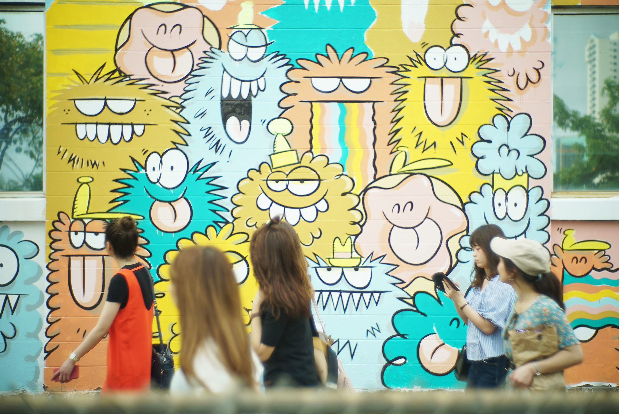 <p>Visitors stroll past Kevin Lyons' mural in progress.</p>