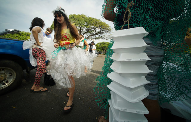 Anti plastic bag and anti styrofoam marchers make final adjustments to their costumes at Magic Island before heading by bus to pali Longs Drugs. 10 feb 2017