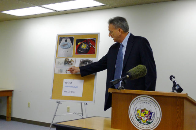 Stephen Levins, executive director of Hawaii's Office of Consumer Protection, gestures to photos of metal shards released when air bags exploded on Wednesday, May 24, 2017, in Honolulu. Hawaii is suing auto manufacturers Ford, Nissan and Toyota over air bags that can spew shrapnel when they deploy. The complaint filed Wednesday says the manufacturers knew or should have known for more than a decade that air bags installed in their cars posed serious and sometimes fatal danger.  (AP Photo/Cathy Bussewitz)