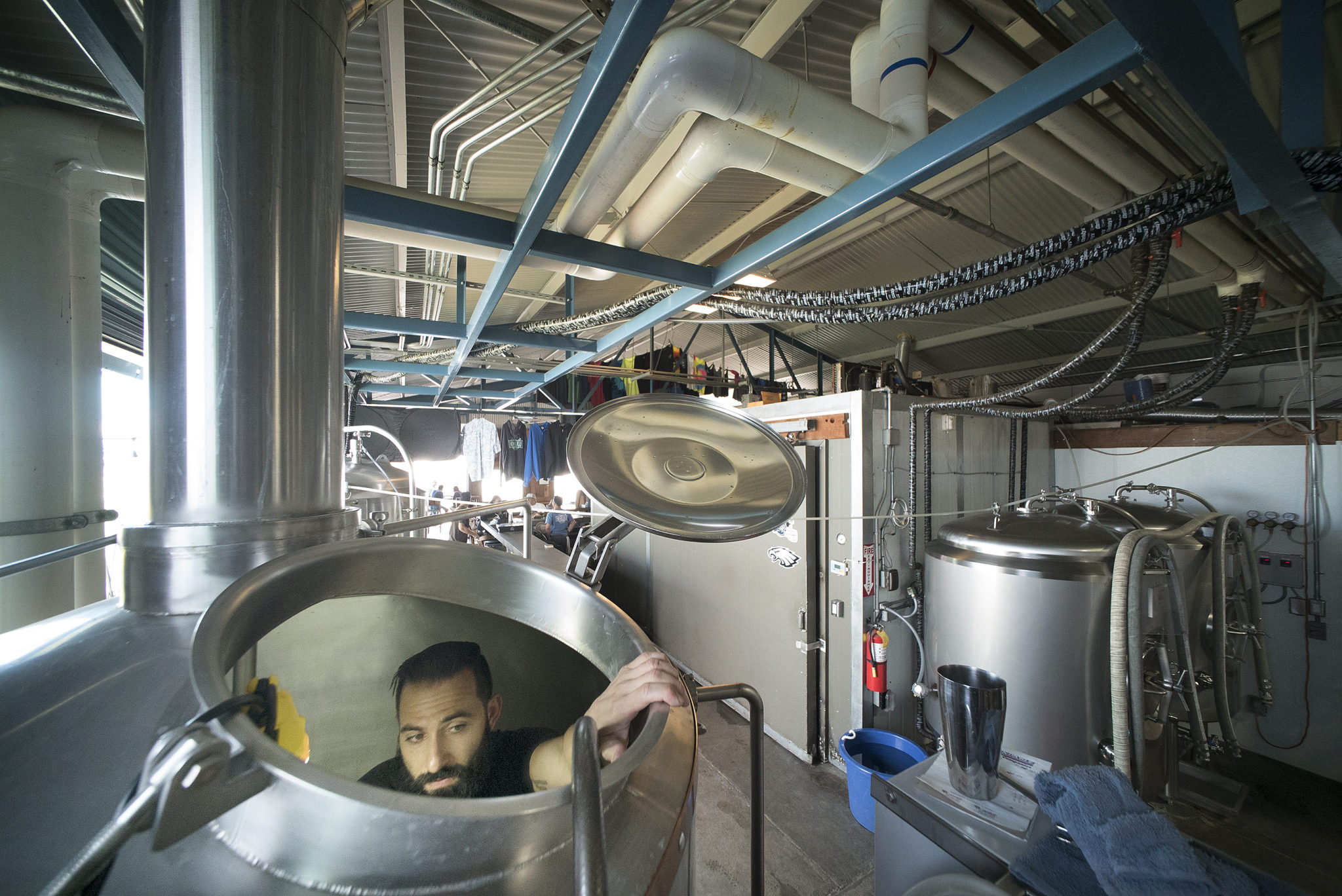 <p>After climbing through a small opening at the top of the wort kettle, Caldwell scrubs the stainless steel inner chamber with a scouring pad.</p>