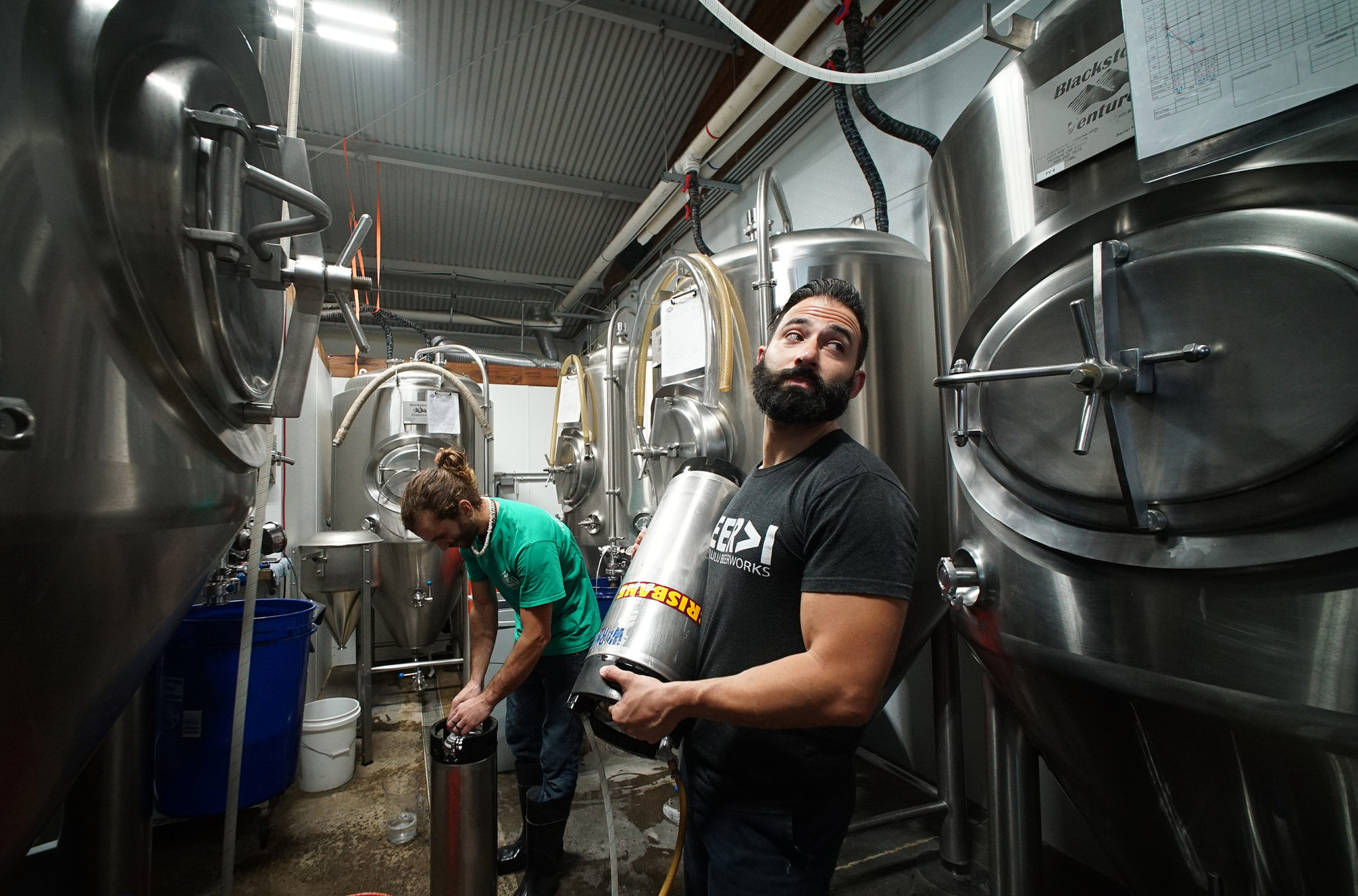 <p>Direnzo and Ken Caldwell prepare to place yeast into the fermentation vessel.</p>