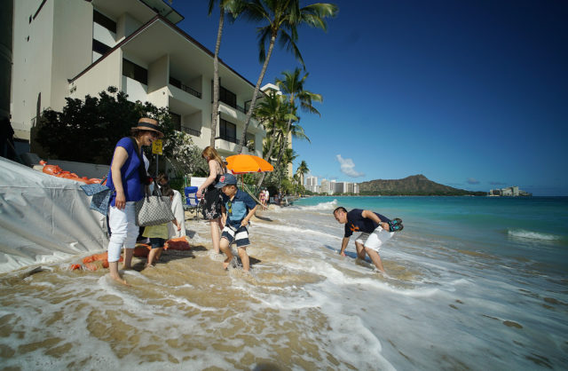 Visitors walk thru shorebreak waves fronting the Outrigger Reef Waikiki Beach Resort after high tide. 25 may 2017