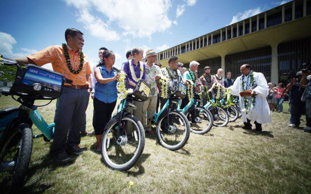 Biki bicycle sharing bikes are ceremoniously blessed with rainwater and ti leaf on the lawn at the Capitol.