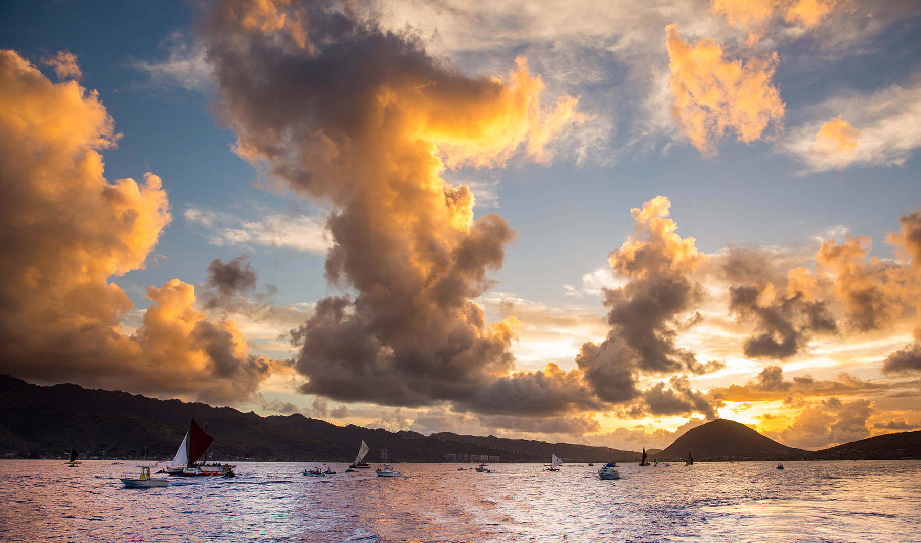 <p>The sun rises over Hawaii Kai as the Hokulea begins its journey from Maunalua Bay to Magic Island. Photograph Anthony Quintano/Civil Beat</p>