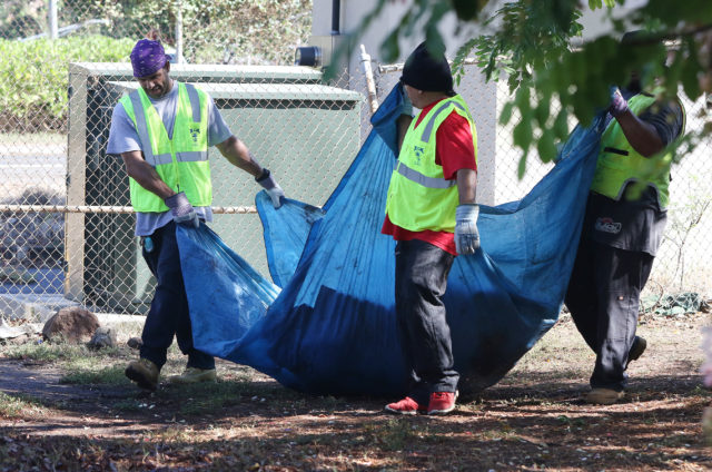 Hala Toa Mui (HTM) Construction Inc workers clean homeless debris along the freeway at the rear of Nuuanu YMCA.