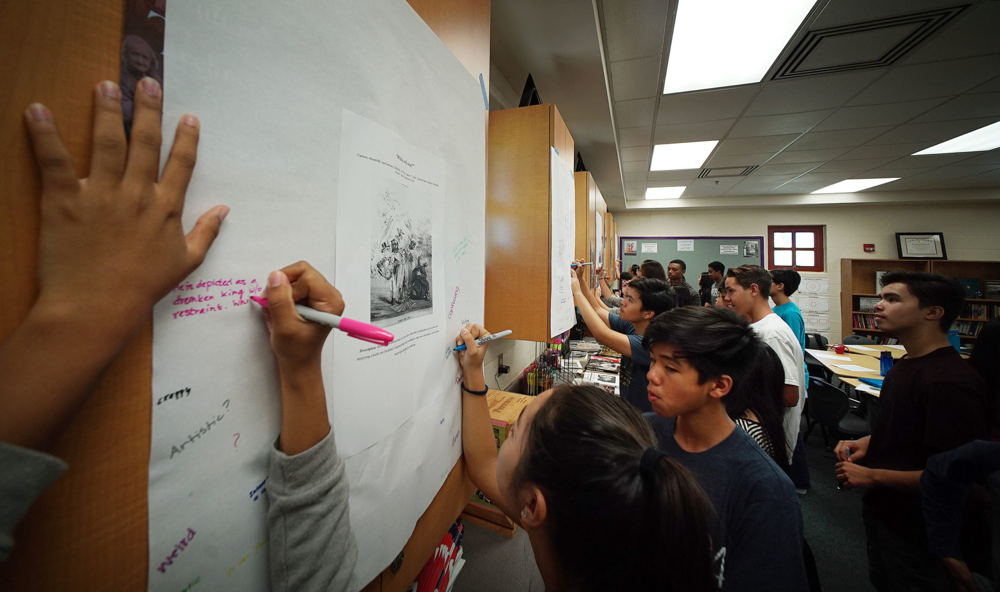 9th graders in Mililani High School's, Mrs. Amy Perruso social studies class write comments and observations on 2 cartoons of King David Kalakaua in the late 1800s.