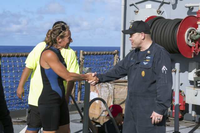 In this Wednesday, Oct. 25, 2017 photo, USS Ashland Command Master Chief Gary Wise welcomes aboard Jennifer Appel, an American mariner, one of two Honolulu women and their dogs who were rescued after being lost at sea for several months while trying to sail from Hawaii to Tahiti. The U.S. Navy rescued the women on Wednesday after a Taiwanese fishing vessel spotted them about 900 miles southeast of Japan on Tuesday and alerted the U.S. Coast Guard. The women, identified by the Navy as Jennifer Appel and Tasha Fuiaba, lost their engine in bad weather in late May, but believed they could still reach Tahiti. (Mass Communication Specialist 3rd Class Jonathan Clay/U.S. Navy via AP)