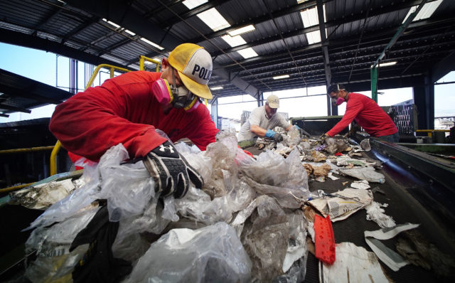 Workers pull plastic off of conveyor belt at RRR Recycling Services Hawaii.