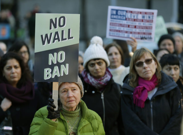 """Annie Phillips, of Burien, Wash., holds a sign that reads """"No Wall No Ban,"""" during a protest, Wednesday, Dec. 6, 2017, outside a federal courthouse in Seattle. The U.S. Supreme Court decision allowing President Donald Trump's third travel ban to take effect has intensified the attention on a legal showdown Wednesday before three judges in Seattle who have been cool to the policy as they hear arguments in Hawaii's challenge to the ban, which restricts travel to the United States by residents of six mostly Muslim countries and has been reviled by critics as discriminatory. (AP Photo/Ted S. Warren)"""