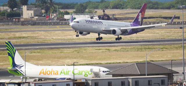 Hawaiian Airlines jet lands at Daniel Inouye Airport with foreground, Aloha Air Cargo.