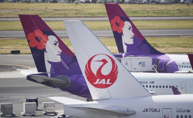 JAL Japan Airlines jet and Hawaiian Airlines sit at Daniel Inouye International Airport.
