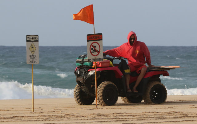 Ocean Safety out at North Shore / Pupukea as lifeguard moves signs in anticipation of larger swells.