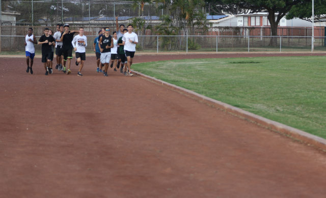 Campbell High School students run on their dirt track that encircles their grass football field.
