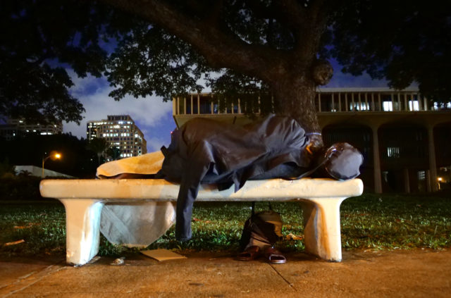Person sleeps on bench along Punchbowl Street on opening morning of the 2018 Legislature.