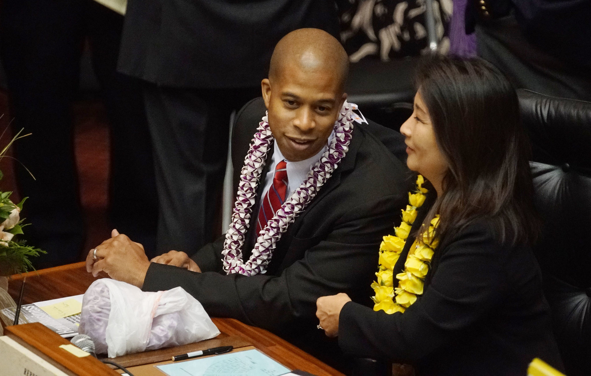 Rep Justin Woodson chats with Rep Sylvia Luke before State of State on the House floor.