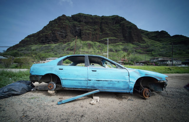 Abandoned car at Nanakuli along Farrington Highway with the Puu Ohulu (mountain). Waianae