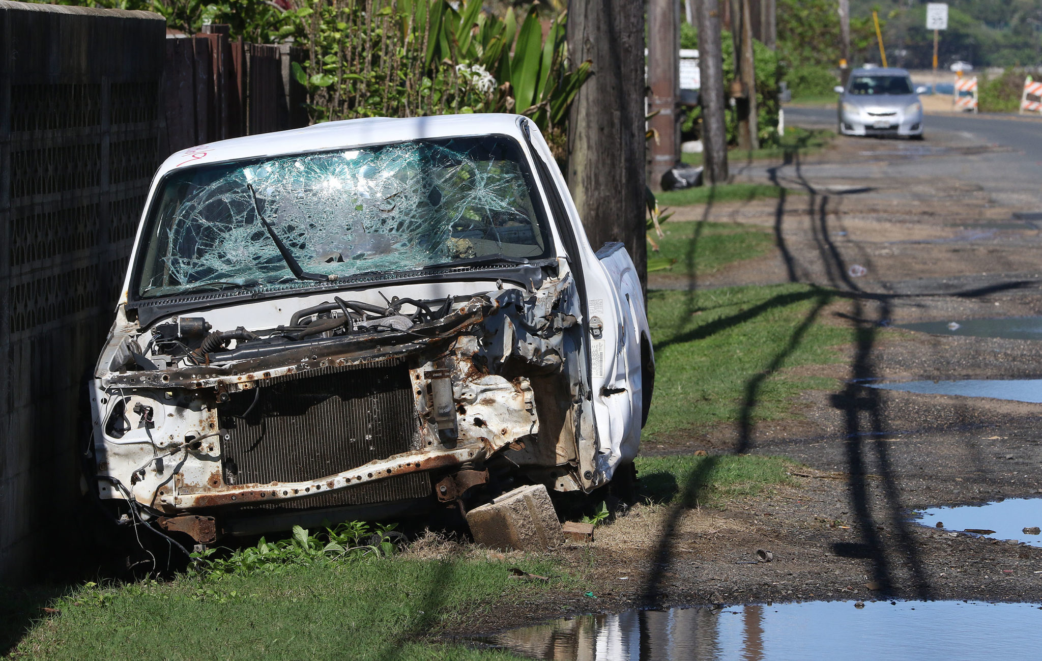 <p>Abandoned cars like this one on the North Shore are often stripped of valuable parts, leaving metal, broken glass and wires behind on the side of the road.</p>