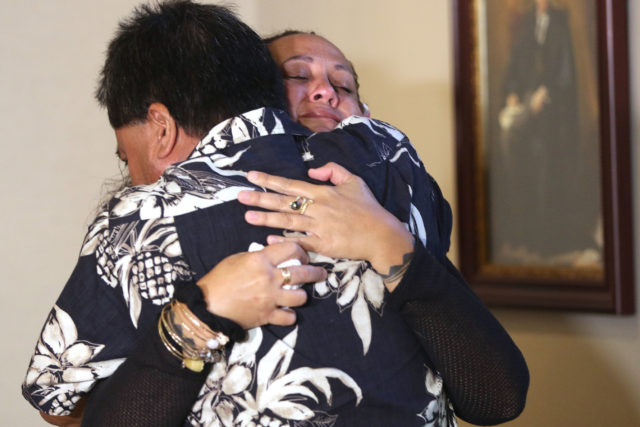 Survivor Alika Bajo hugs Malia Lum Marquez, sister of Anthony Thomas Lum at press conference held at Mark Davis' offices to announce the $80 million settlement with Kamehameha Schools.